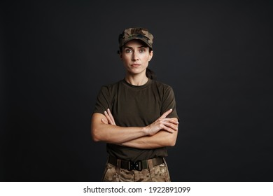 Confident beautiful soldier woman standing isolated over black background, arms folded - Shutterstock ID 1922891099