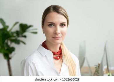 Confident beautiful young businesswoman looking at camera, ambitious serious lady entrepreneur posing in office, independent attractive woman or successful female business owner head shot portrait