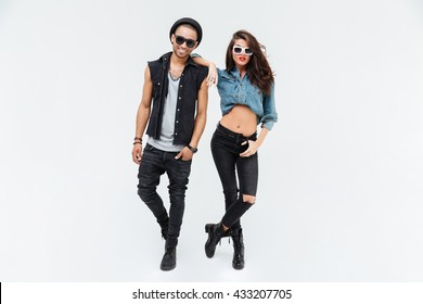 Confident beautiful young couple standing together over white background