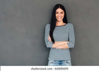 Confident beauty. Attractive young woman keeping arms crossed and looking at camera with smile while standing against grey background