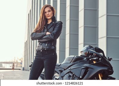 A confident biker girl with her arms crossed next to her superbike outside a building.