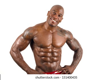 Confident black bodybuilder smiling. Strong man with perfect abs, shoulders,biceps, triceps and chest. Isolated on white background