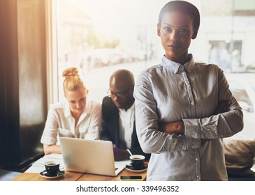 Confident black business woman standing in front of colleagues