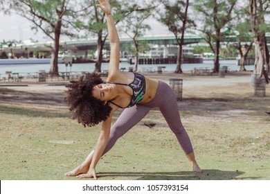 Confident black girl with eyes closed bending on side and stretching body in yoga asana training in park.