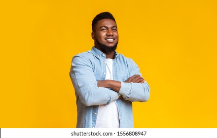 Confident black millenmial man standing with his arms crossed, smiling and looking at camera, yellow studio background with copy space