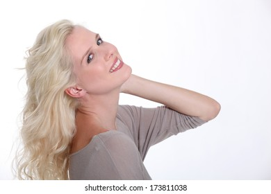 Confident blond woman posing on a white background