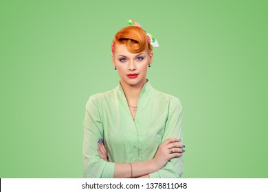Confident and bossy. Closeup portrait beautiful pinup girl businesswoman looking at camera arms crossed, folded isolated on green background wall. Retro vintage 50s style lady. Neutral face expression