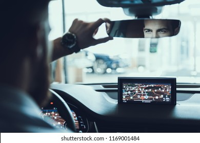 Confident Buisiness Man Look At Back Car Mirrow. Portrait of Handsome Caucasian Bearded Stylish Person Driving Car in Town Using Road GPS Navigator. Auto Driving Concept