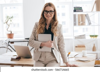 Confident business expert. Attractive young smiling woman in smart casual wear holding digital tablet and looking at camera while leaning on desk in creative office
