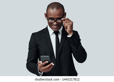 Confident business expert. Charming young African man in formalwear using smart phone and smiling while standing against grey background
