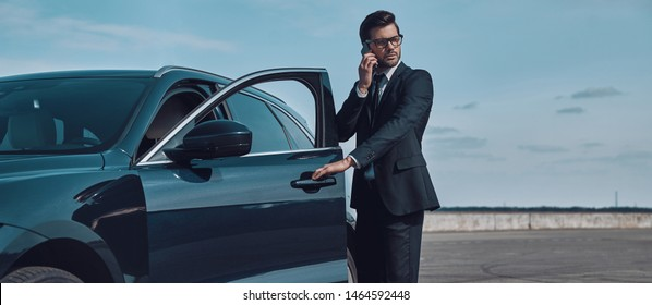 Confident business expert. Full length of handsome young businessman talking on the phone while entering his car outdoors