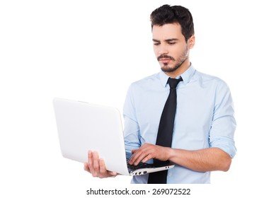 Confident business expert. Handsome young man in shirt and tie working on laptop while standing against white background