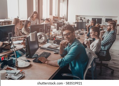 Confident business expert. Handsome young man looking at camera and holding hand on chin while working together with his colleagues in office