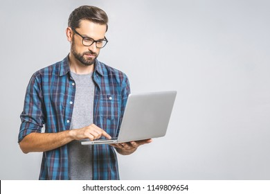 Confident business expert. Confident thoughtful young handsome man in shirt holding laptop while standing against grey background
