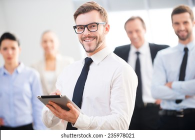 Confident business expert. Confident young businessman holding digital tablet and smiling while his colleagues standing in the background