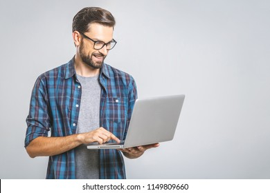 Confident business expert. Confident young handsome man in shirt holding laptop and smiling while standing against grey background