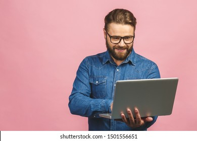 Confident business expert. Confident young handsome man in casual holding laptop and smiling while standing against isolated pink background.
