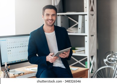 Confident business expert. Confident young man holding digital tablet and smiling while leaning at the deck in office