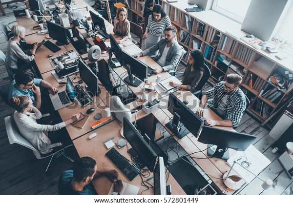 Confident business experts a work. Top view of group of young business people in smart casual wear working together while sitting at the large office desk