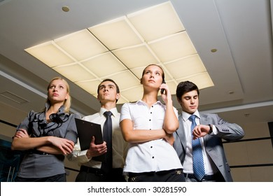 Confident business lady calling by cell with several partners behind and looking upwards attentively