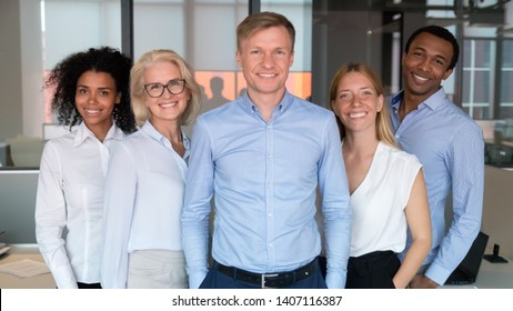 Confident business man coach boss chief corporate leader company owner looking at camera with multiracial team people, professional manager ceo employer posing with employees office group, portrait