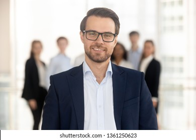 Confident business man coach in suit director company owner professional manager looking at camera with team on background, smiling male ceo leader banker employer posing in office, headshot portrait