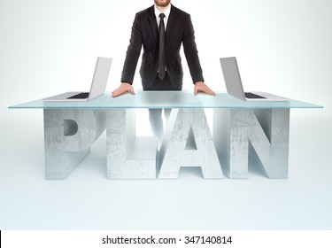 Confident business man leaning on PLAN table with open laptops Bussines concept