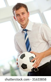 Confident business man standing with a football at an office