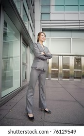 Confident business manager woman standing and looking, full length portrait outside of modern buildings.