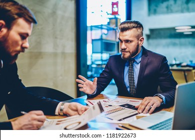 Confident business partners in formal suits sitting at desktop with accountings and documentation discussing plans for cooperation, professional male economists talking about corporate income
