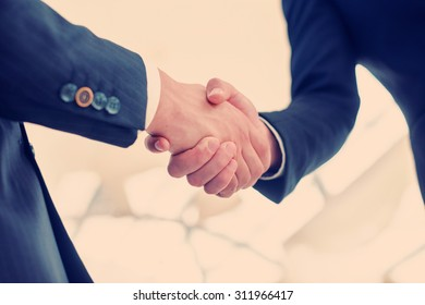 Confident business partners handshaking. Two Confident businessman shake hands with each other in the business office view from below