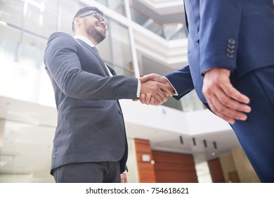Confident business partners shaking hands after successful completion of negotiations, interior of modern office lobby on background, low angle view