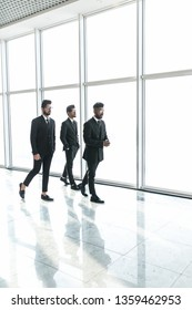 Confident business partners walking down in office building and talking about new project.