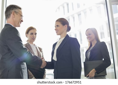 Confident business people shaking hands in office