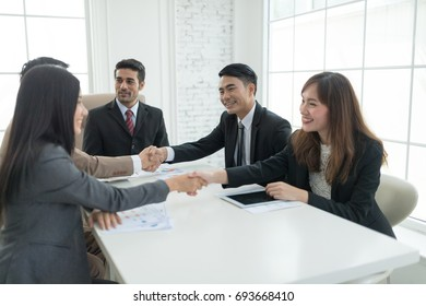 A confident business team of mixed ages and ethnicity making handshaking while meeting in a modern office. They are discussing ideas for their business development.