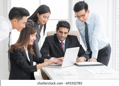 A confident business team of mixed ages using labtop computer thegether for meeting in a modern office. They are discussing ideas for their business development.In selective focus on face.