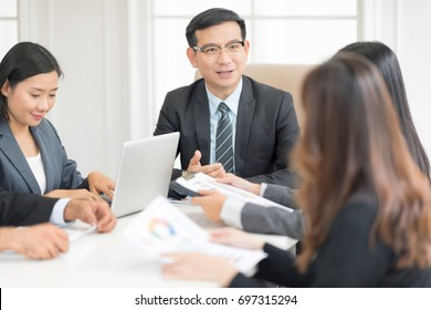 A confident business team of mixed ages and ethnicity are holding a meeting in a modern office. They are discussing ideas for their business development.In selective focus on face