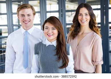 Confident business team smiling at camera in office