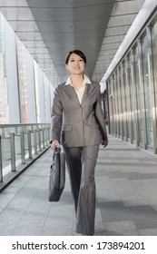 Confident business woman holding briefcase and walking in modern city.