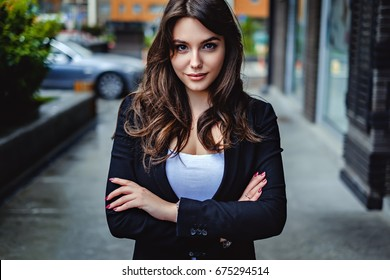 Confident business woman looking at the camera while standing on the street with hands crossed