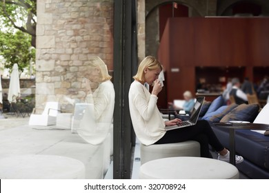 Confident business woman looking at laptop computer screen and drink cafe female freelancer at distance work via net-book enjoying her cup of tea, young caucasian student learn on-line at coffee shop