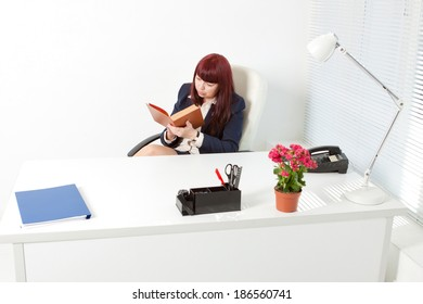Confident business woman in a modern office reading book