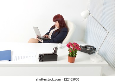 Confident business woman with notebook in a comfortable modern office