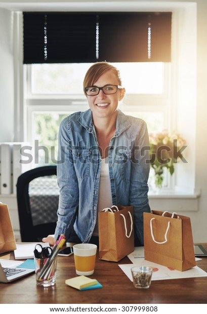 Confident business woman at office standing over desk