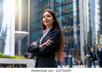 Confident business woman portrait in the City of London; businesswoman standing cross-armed, proud and successful in suit