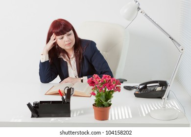 Confident business woman reads book in a comfortable modern office