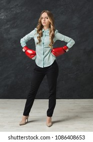 Confident business woman in red boxing gloves punch to the goal. Ready to fight in corporate battle, business competition and perseverance concept, black studio background