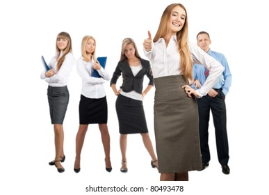 Confident business woman showing thumbs up with her colleagues standing in the background. Isolated on white