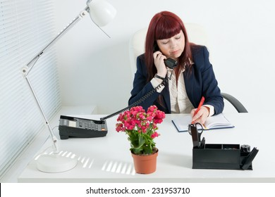 Confident business woman speaks by phone and writes in notebook