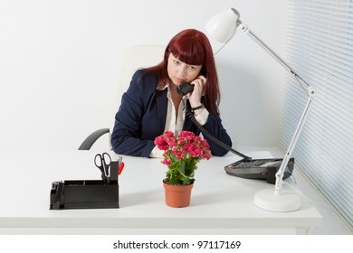 Confident business woman speaks by phone  in a comfortable modern office